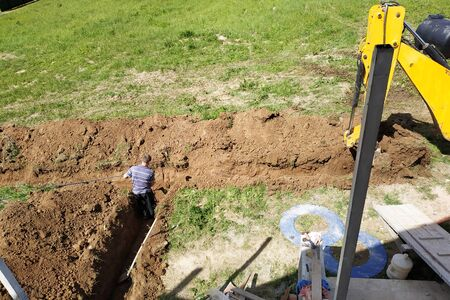 The excavator digs a trench to lay the electric cable. 2019