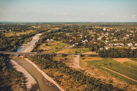 Village and bridge over river view from the top beautiful Carpathian mountains and vast field. 2019