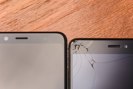 Broken Smart Phone Glass and Broken Smart Phone Glass on a Wood Table.