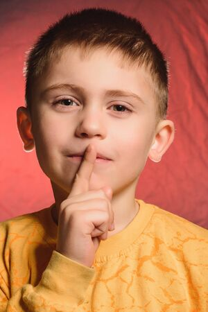 The boy with his index finger shows the sign quietly. Stok Fotoğraf