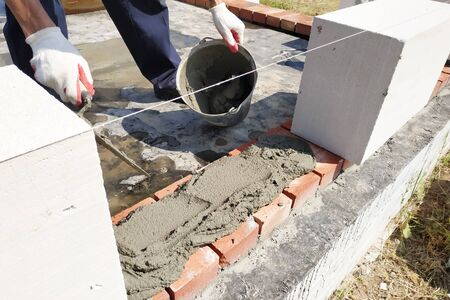 The worker begins the first row of masonry construction in white gas blocks. 2019 Stock fotó