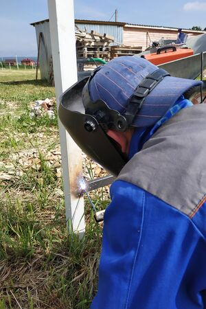 In the village on the construction site, a welder welds a fence.