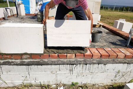 Using a glue solution, the worker begins to build a wall of gas blocks.