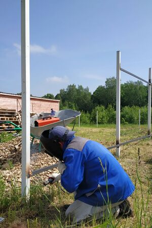 A fence installer welds a metal profile to a new fence post.