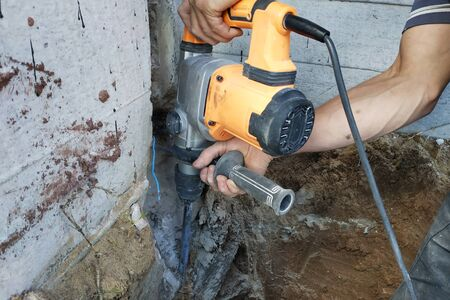 Construction industry worker using pneumatic hammer drill to cut the wall concrete brick, close up