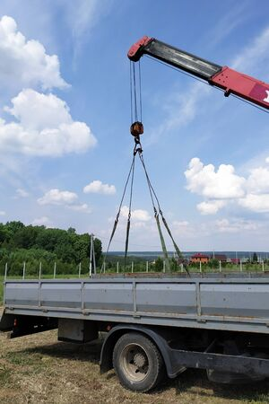 The car crane transports the metal profile from the car body. 2019 Stockfoto