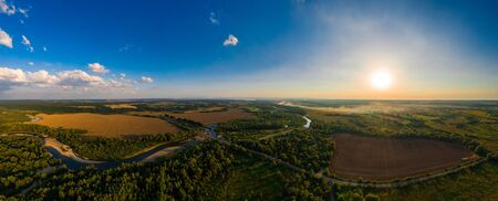 Sunflower field on fertile black earths of Ukraine, on the horizon a beautiful sunset, panorama. 2019 Stok Fotoğraf
