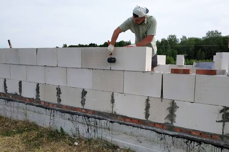 The master performs construction work, namely, laying a wall of gas blocks with tools and adhesive mortar, in the background the sky and the forest. 2019