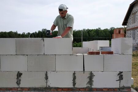 The master performs construction work, namely, laying a wall of gas blocks with tools and adhesive mortar, in the background the sky and the forest