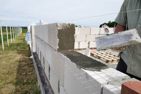 A construction site worker puts a block on the masonry wall and uses glue and auxiliary tools. 2019