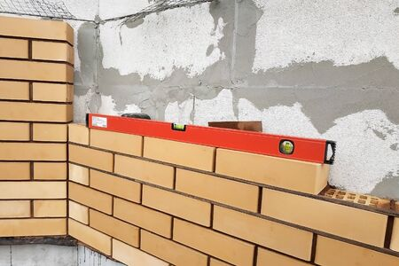 The master after laying the level to the brick, looks at the level horizontally. 2019