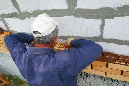 The master builds a wall from the front brick in the village. 2019