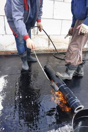 The master works with the assistant to work on the waterproofing of the surface. 2019 Stok Fotoğraf