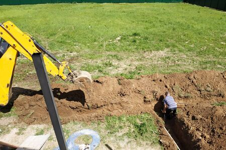 The excavator digs a trench in a private area to lay the electrical cable to the house. 2019 Stok Fotoğraf