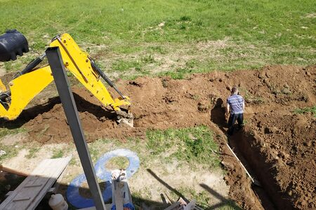 The excavator digs a trench in a private area to lay the electrical cable to the house. 2019 Stockfoto