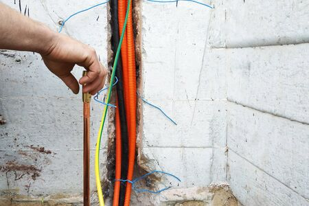 The electrician conducts electrical work on the current grounding of the current drain. 2019