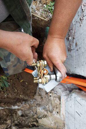 The master performs welding of a copper tube near a dwelling house. 2019