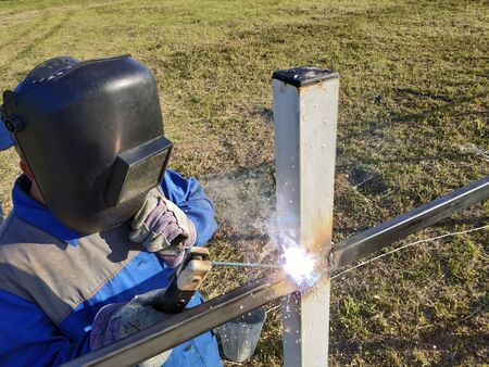 Welding of metal profile to pipes by master outdoors. 2019