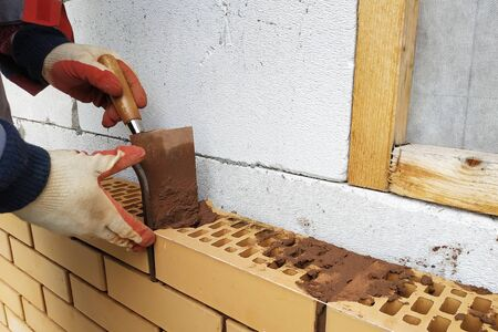 In the summer day the master builds the facade of the house made of red brick. 2019