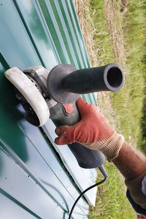 During the roofing work, a construction worker sprays a steel sheet with a trapezoidal profile with an angle grinder. 2019