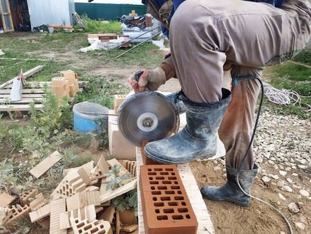 The worker cuts a corner brick with a front facade brick in the countryside. 2019