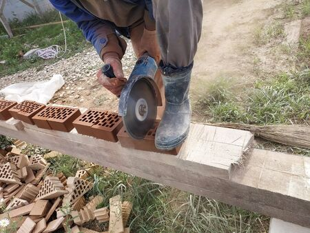 Cutting bricks with an angle grinder in a rural yard. 2019