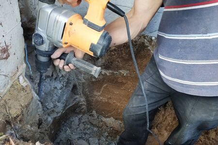 Construction industry worker using pneumatic hammer drill to cut the wall concrete brick, close up. 2019 Imagens