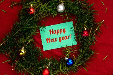 Inscription Happy New Year placed in a wreath from a Christmas tree with balls on a red background with a top view 2020
