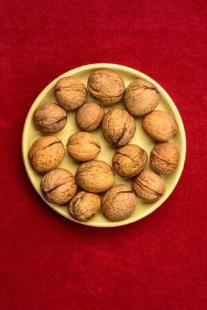 Walnuts in a plate on a red background. 2019
