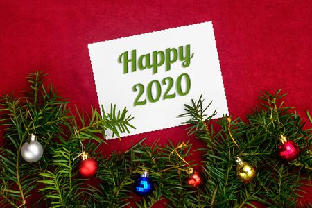Christmas and New Year composition with numbers 2020 and branches of Christmas tree with balls on red background with top view 2021 Stock Photo
