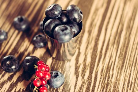 Delicious fruit berries in a small metal bowl, blue berry and red currant. 2019