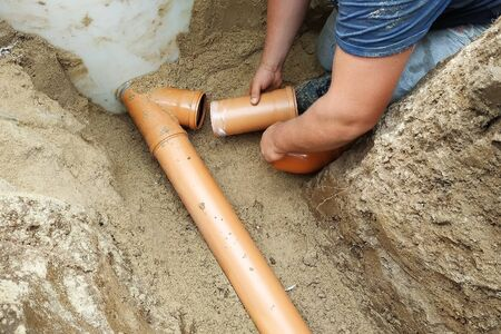 Supply of a sewer pipe to a sump on a trench in the village. 2019