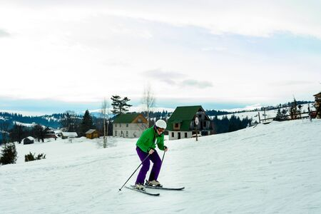 Young man in green jacket and purple pants skiing. 2018 Banque d'images - 131975521