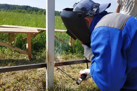 At the construction site, the master welds a metal profile for the fence. 2019 Reklamní fotografie