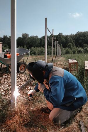 The welder welds a new metal frame for the fence around the house in the village. 2019