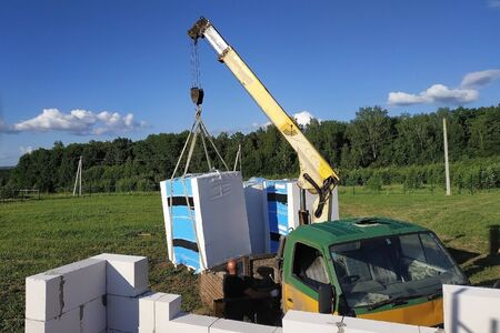 The process of loading and unloading using a mobile crane blocks and bricks for construction. 2019 Stock Photo