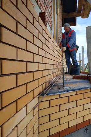 The master builds a wall of a house from a front brick. 2019
