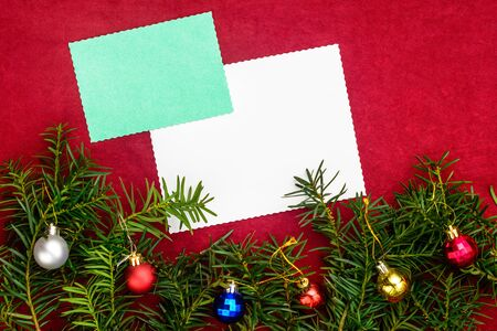Piece of paper for Christmas wishes on a red background with branches of Christmas tree and Christmas balls. 2019