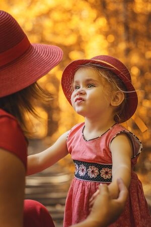 Mom with daughter in red hats walking in autumn in tunnel of love. 2019