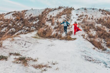 Beautiful couple walks in the phosphate-gypsum white mountains of Ukraine, the girl in a red dress. 2019 Zdjęcie Seryjne