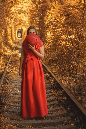 Beautiful woman in red autumn dress walks the tunnel of love. 2019 Zdjęcie Seryjne