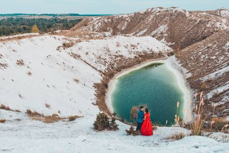 Beautiful couple walking in the phosphate-gypsum white mountains of Ukraine, the girl in a red dress on a background of a green lake. 2019