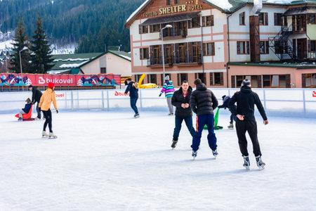 Bukovel, Ukraine February 12, 2019 - girl in a yellow sweater ice skating instructor in Bukovel. 2019 新聞圖片