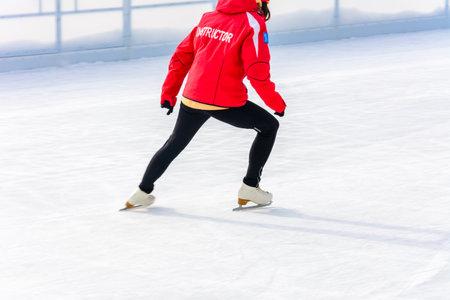 Bukovel, Ukraine February 12, 2019 - girl in a red jacket ice skating instructor in Bukovel. 2019