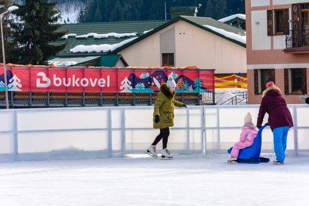 Bukovel, Ukraine February 12, 2019 - little girl roller skates with adults. 2019