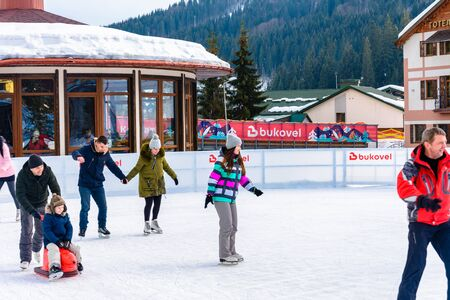 Bukovel, Ukraine February 12, 2019 - young couple roller skating for the first time. 2019