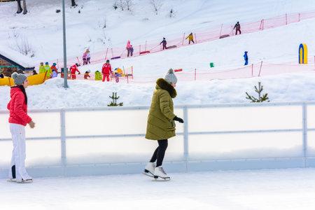 Bukovel, Ukraine February 12, 2019 - girl in green jacket skates on ice. 2019