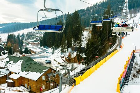 Lift and ski slope with skiers below it on a sunny winter day with blue sky, ski resort Bukovel. 2019