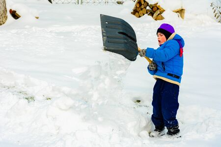 Little boy with big shovel removes snow after a snowstorm. 2019