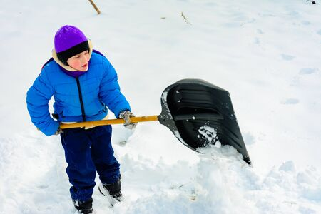 Smiling boy is carrying snow on a shovel, Child cleans the yard after a snowfall. 2019